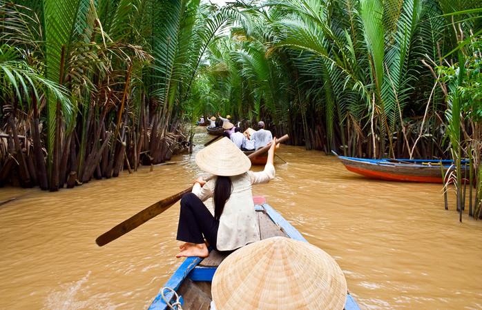 Vietnamese vrouw aan het roeien in een boot in de Mekong Rivier, Vietnam.